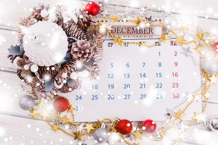 Weihnachtskomposition. Weihnachtsgeschenk, gestrickte Decke, Tannenzapfen, Tannenzweige auf weißem Holzhintergrund. Flache Lage, Draufsicht, Kopierraum
