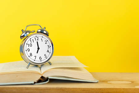 Silver vintage alarm clock with books on yellow background