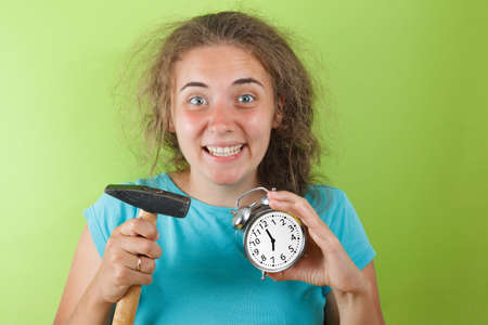 Portrait of shocked girl holding round clock isolated and hummer on yellow wall background in studio. People sincere emotions, lifestyle concept. Mock up copy space 写真素材