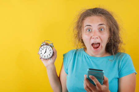 Portrait of shocked girl holding round clock isolated on yellow wall background in studio. People sincere emotions, lifestyle concept. Mock up copy space