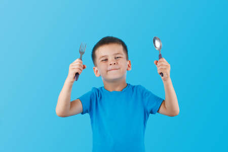 Funny Little Handsome Boy with Fork and Knife. Hungry Child. Smiling Kid. Want to eat. Place for text