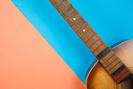 Acoustic guitar resting on color background with copy space. Modern concept