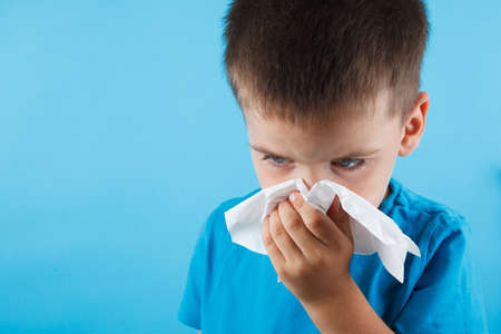 Child blow the nose. Asian boy using tissue to wipe snot from his nose and free form copy space. Illness child with allergy symptom. Isolated on blue background. Studio shot. 写真素材 - 130135424