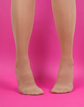 Legs of young caucasian woman in black tights on pink background