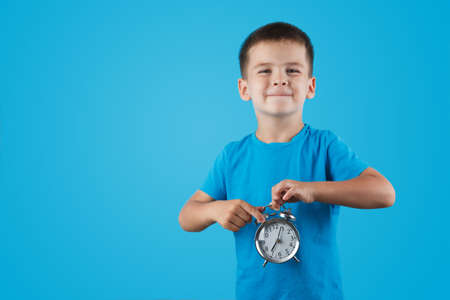 kid boy holding clock alarm, copy space. Time for school. Little student overslept.