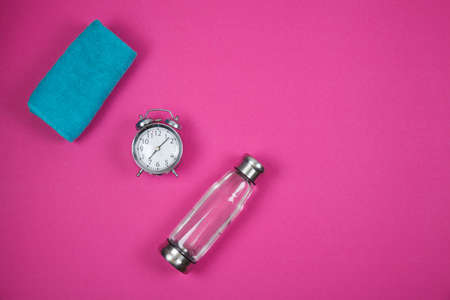 Alarm clock and fitness equipment with bottle on color background