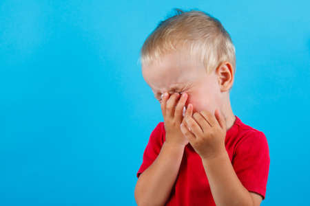 Child blow the nose. Asian boy using tissue to wipe snot from his nose and free form copy space. Illness child with allergy symptom. Isolated on blue background. Studio shot.