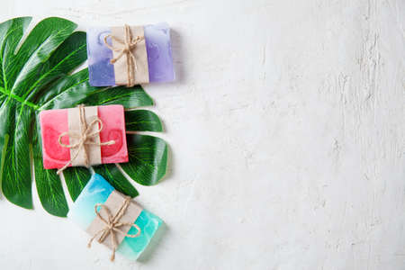 Spa composition with tropical leaves on a white background .Different organic soap, care and beauty concept, top view