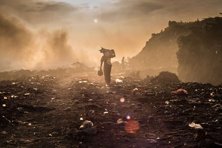 picker: A waste picker is collecting reusable or recyclable materials in a open burning dump.