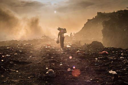 recolector de basura: Un reciclador está recogiendo materiales reutilizables o reciclables en un vertedero de quema a cielo abierto.