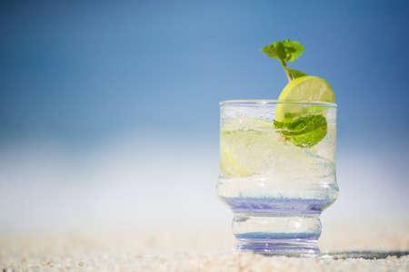glass of lemonide on a sandy beach