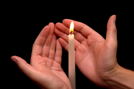 god s hand: hand near the candle on a black background