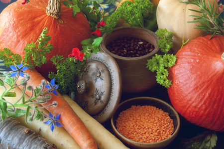 Pumpkins seeds butternut squash carrots and herbs Still life composition with seasonal vegetables of autumn