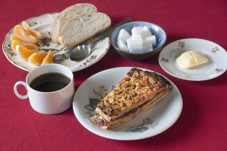 Breakfast set with coffee cake bread butter and orange wedges