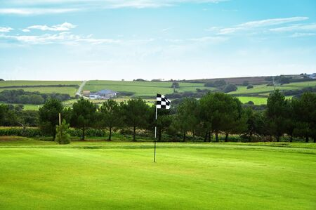 Golf green with a checkered flag the countryside in background Stok Fotoğraf