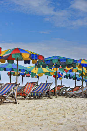 Colourful umbrellas and deck chairs on a white sandy beach. photo