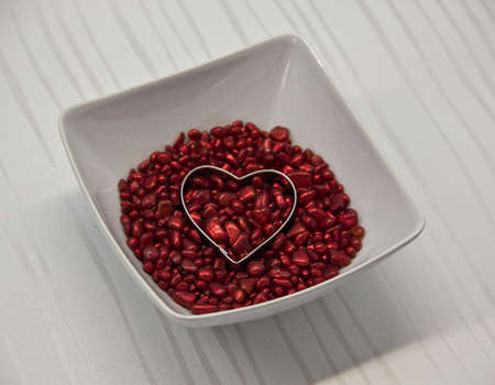 Red decorative stones with a heart in a bowl. photo