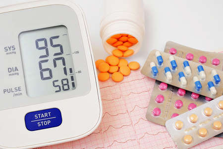 automatic blood pressure meter and pills on cardiogram graph background Stock fotó