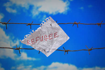 piece of paper with refugee text on barbed wire on blue sky background