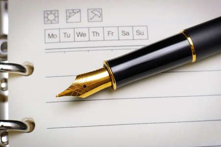 macro of black luxury gold plated fountain pen on open notebook