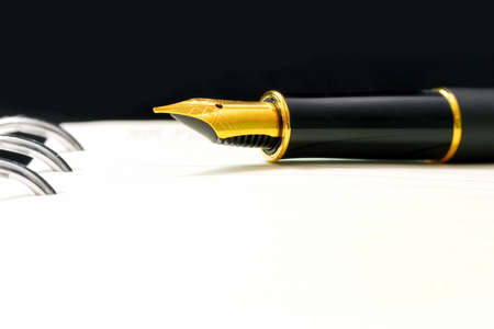 macro of black luxury gold plated fountain pen on open notebook with copy space