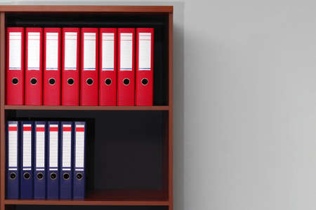 red and blue office ring binder folders on shelves with copy space Archivio Fotografico