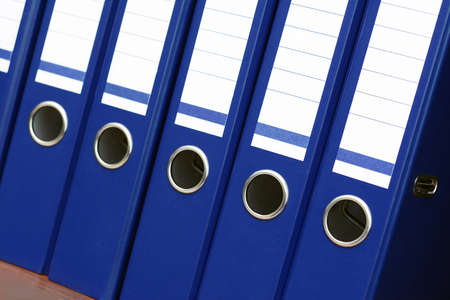 closeup of blue file binders in a row on a shelf