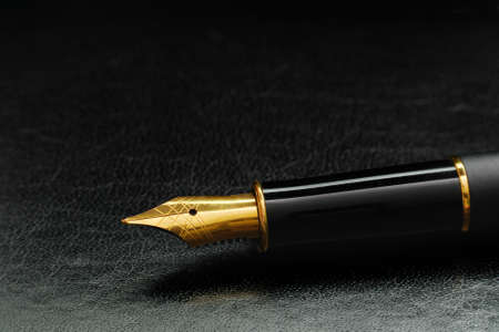 macro of luxury black gold plated fountain pen on black leather with copy space