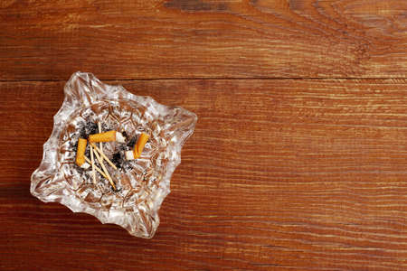 top view of cigarette butts in a glass ashtray on a wooden background with copy space