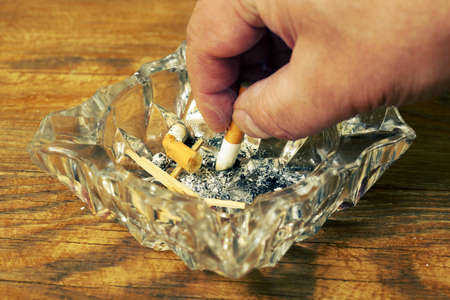 close-up of hand putting out cigarette in a glass ashtray, color graded