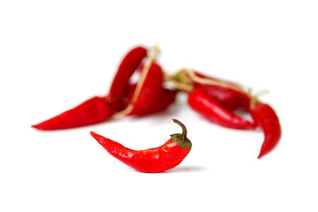 red dry chili pepper in front of bunch of other peppers on white background Zdjęcie Seryjne