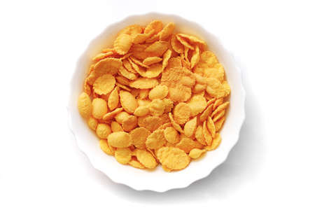 closeup of corn flakes in a white bowl isolated on white background, top view