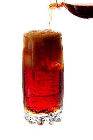pouring cola into a glass with ice cubes, isolated on white background Foto de archivo