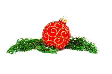 red christmas ball with green pine tree branches isolated on white background