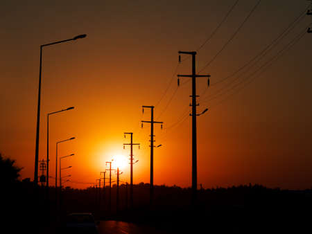 road with power line and lamp posts in sunset
