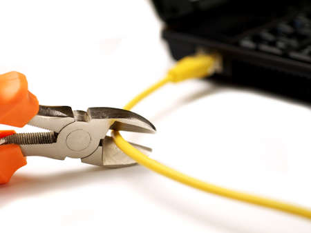 wire cutter cutting network cable from laptop on white background, shallow depth of field, selective focus Stock fotó