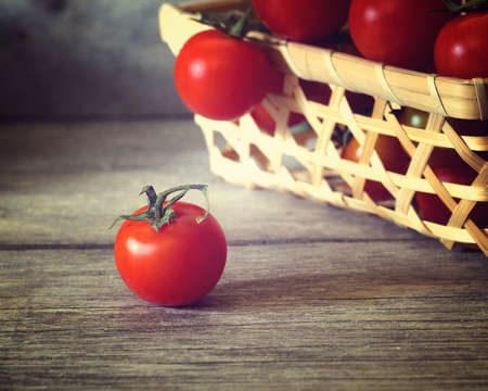 ripe cherry tomato on wooden table and basket of tomatoes in background, shallow depth of field,   vintage colors Stock fotó