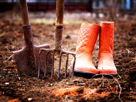shovel, pitchfork and orange rubber boots in soil in spring garden, shallow depth of field, toned Stock fotó