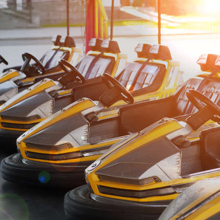 electric bumper cars in a row in amusement park in the morning, toned in sunlight effect with lens flare
