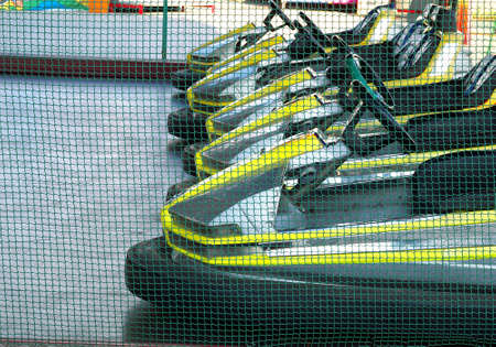 eelctric bumper cars in a row in amusement park behind the fence