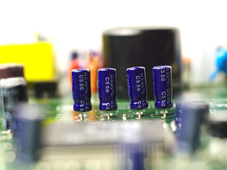 four electrolytic capacitors mounted on printed circuit board in a row, shallow depth of field Stock fotó