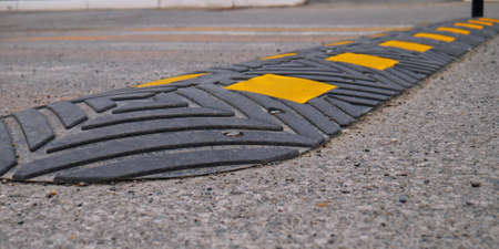 Bolted down speed bump made of rubber on asphalt road, closeup Stock fotó