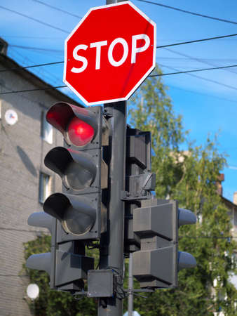 red light on traffic light and stop sign above it