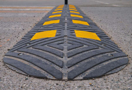Bolted down speed bump made of rubber on asphalt road, closeup