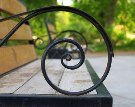 Wooden bench armrest made from hand forged spiral rod, shallow depth of field