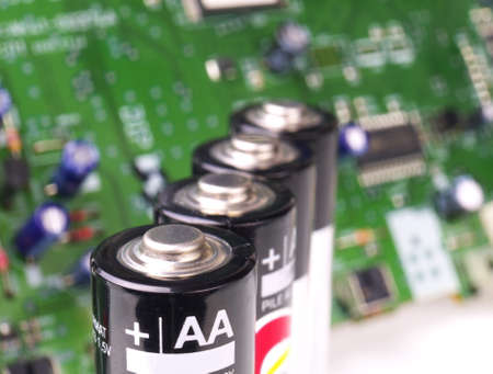 four AA batteries in a row in front of circuit board, macro, shallow depth of field