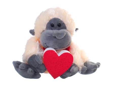 monkey soft toy holding red heart symbol on white background Stock fotó