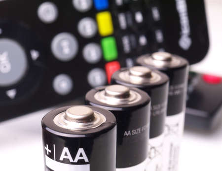 four AA batteries in a row in front of remote control, macro, shallow depth of field Фото со стока