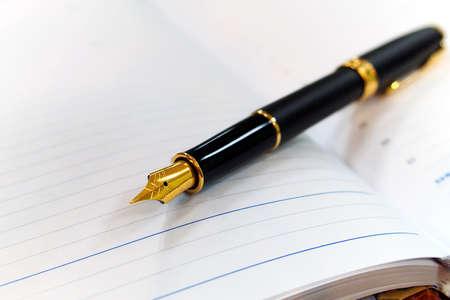 golden fountain pen on open notebook