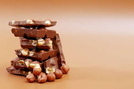 stack of milk chocolate pieces and hazelnuts on brown background with copy space